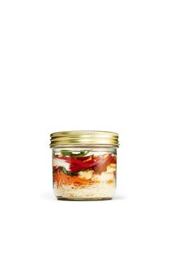 Vegetables in airtight jar isolated against white background
