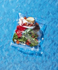 Vegetables packed in zipper storage bag over blue background