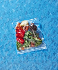 Vegetables packed in zipper storage bag over blue background