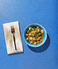 Overhead view of food served in bowl over blue background