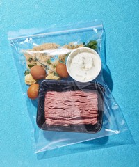 Close up of food packed in zipper storage bag against blue background