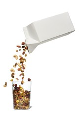 Nuts pouring into glass against white background