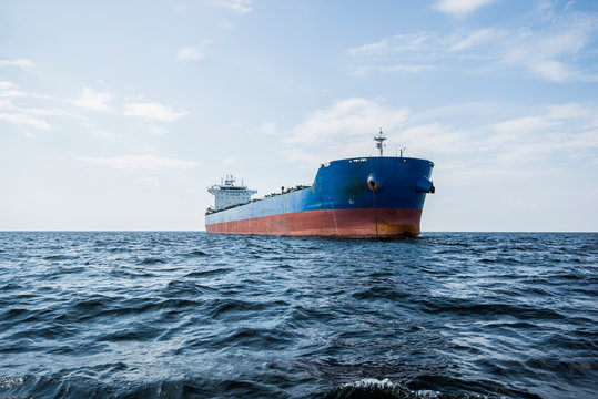 Cargo ship under the cloudy blue sky, Baltic sea, Latvia