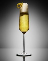 Champagne with sweet lemon peel on gray background
