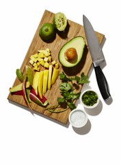 Avocado, lime and coriander on cutting board on white background
