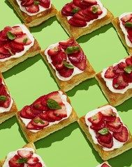 Pastries topped with strawberries and cream on green background