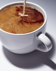 Close up of milk poured into coffee cup