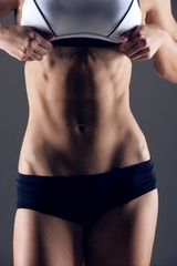 Midsection of woman posing against gray background