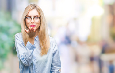 Young beautiful blonde business woman wearing glasses over isolated background looking at the camera blowing a kiss with hand on air being lovely and sexy. Love expression.