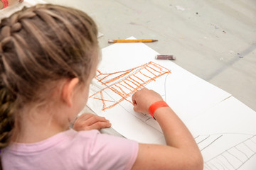 Young girl drawing with crayons