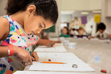 Young girl drawing in a classroom