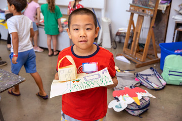 Young boy holding his completed arts and crafts
