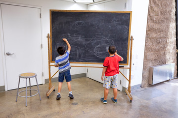 Young boys drawing on a chalkboard