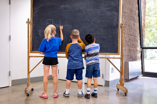 Children writing on a chalkboard