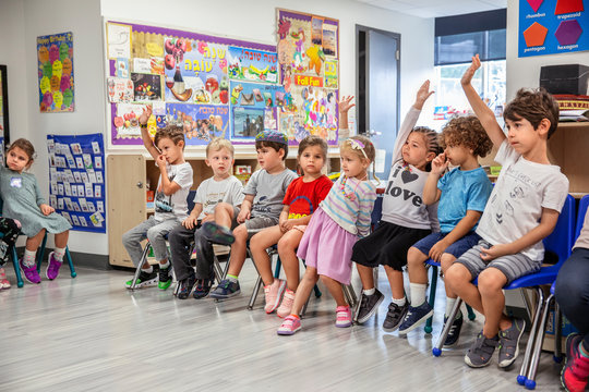 Children raising their hand in a classroom
