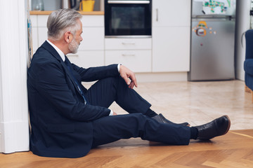 Man in suit sitting on the floor at home