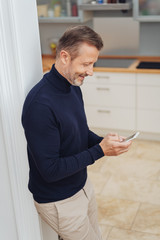 Man leaning on wall at home and using smartphone