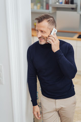 Man talking by the phone at home and smiling
