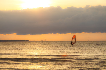 TALLINN, ESTONIA - AUGUST, 10, 2017: Sportman windsurfer on the sea surface against sunset orange sky