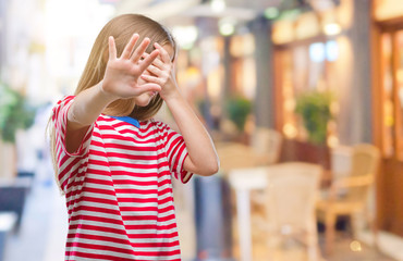 Young beautiful girl over isolated background covering eyes with hands and doing stop gesture with sad and fear expression. Embarrassed and negative concept.