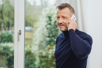Man talking by telephone, standing against window