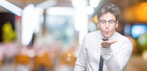 Young business man wearing glasses over isolated background looking at the camera blowing a kiss with hand on air being lovely and sexy. Love expression.