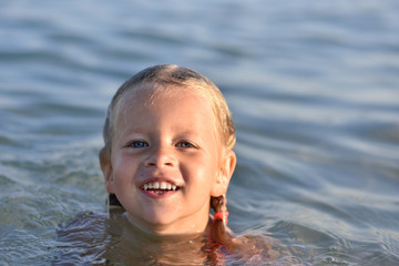 Little girl bathes in the sea, portrait, wet hair
