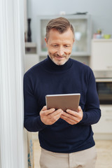 Adult man looking at tablet pc screen and smiling