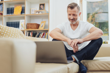 Man sitting on couch and looking at laptop