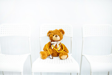 Toy teddy bear with medical stethoscope on the chair on the white background