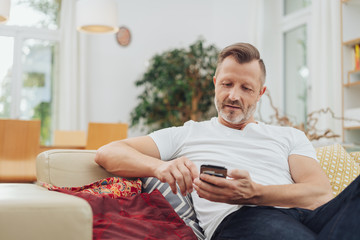 Man on couch, looking at smartphone with interest
