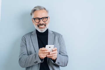 Laughing middle-aged man with smartphone