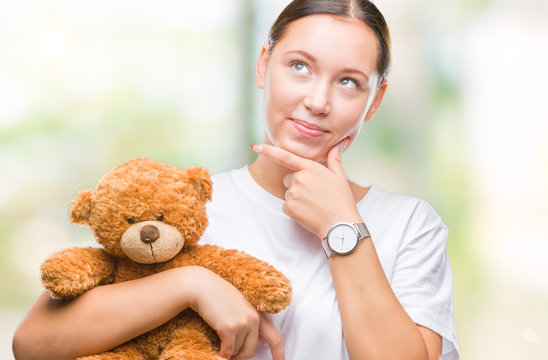 Young caucasian woman holding teddy bear over isolated background serious face thinking about question, very confused idea