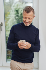 Man texting on his smartphone and smiling