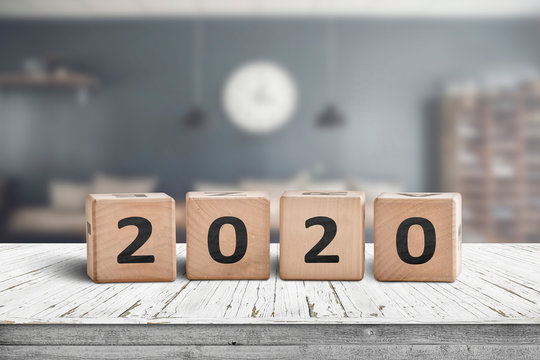 Year 2020 sign on a wooden desk in a cozy kitchen