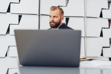 Young businessman behind laptop screen