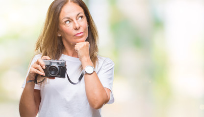 Middle age hispanic woman taking pictures using vintage photo camera over isolated background serious face thinking about question, very confused idea