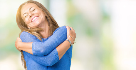 Middle age beautiful woman wearing winter sweater over isolated background Hugging oneself happy and positive, smiling confident. Self love and self care