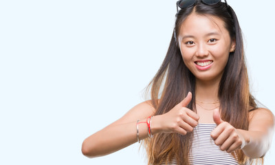 Young asian woman wearing sunglasses over isolated background approving doing positive gesture with hand, thumbs up smiling and happy for success. Looking at the camera, winner gesture.