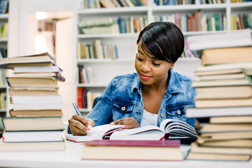Smart african american young woman dressed in casual wear preparing for studying seminar in library.Intelligent dark skinned hipster student writing and reading