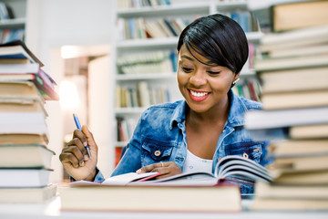 Pretty teenage black african college student girl studying and reading a book in college library