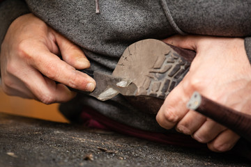 close up of the hands of a man repairing shoes