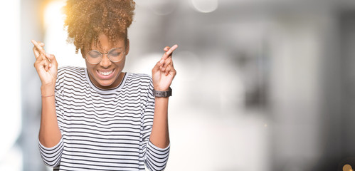 Beautiful young african american woman wearing glasses over isolated background smiling crossing fingers with hope and eyes closed. Luck and superstitious concept.