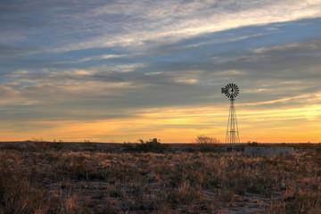 Fotorolgordijn Chocoladebruin Winmill in the Texas Desert at Sunset