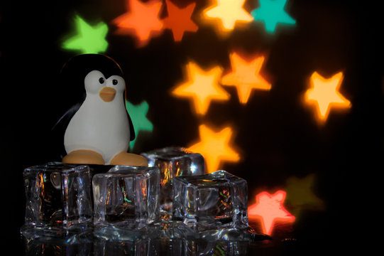 The penguin emblem of free software, Tux, on ice cubes with multicolored stars in the background