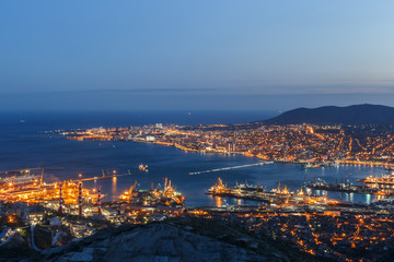 Panoramic view of Novorossiysk City and  Tsemess Bay. Night cityscape of large port at Black Sea coast in Russia