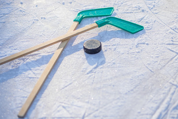 hockey stick and puck on the ice on sunny winter day.winter sports for outdoor activities.hockey puck and stick laying on the textured ice close up copyspace.Young hockey player practising on a frozen