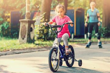 Little girl with helmet riding bike at sunset