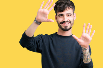 Young handsome man over isolated background Smiling doing frame using hands palms and fingers, camera perspective