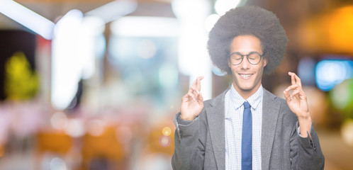Young african american business man with afro hair wearing glasses smiling crossing fingers with hope and eyes closed. Luck and superstitious concept.